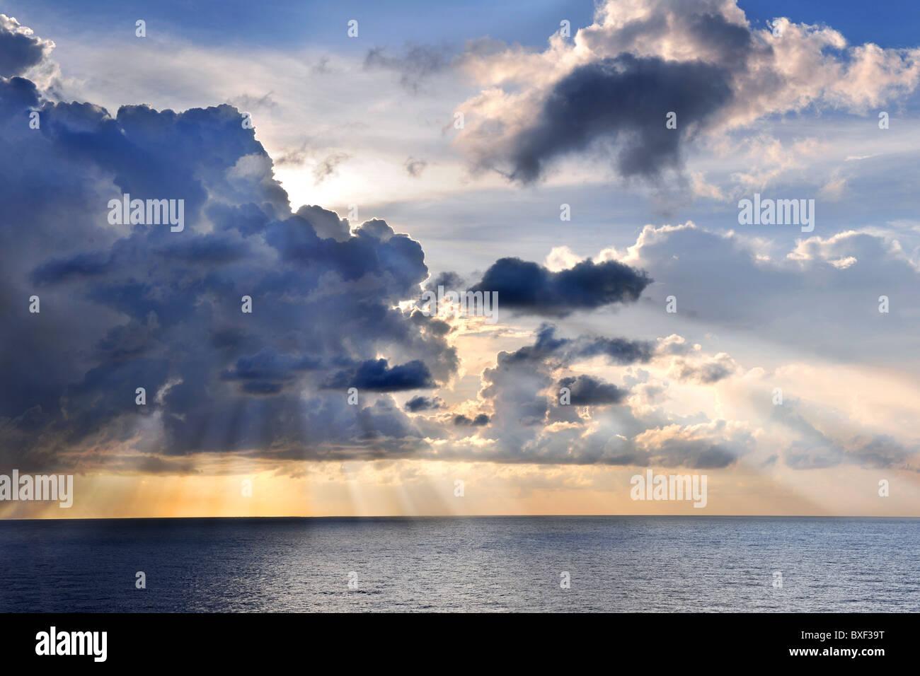 Coucher du soleil des Caraïbes en mer avec les rayons du soleil et nuages Photo Stock