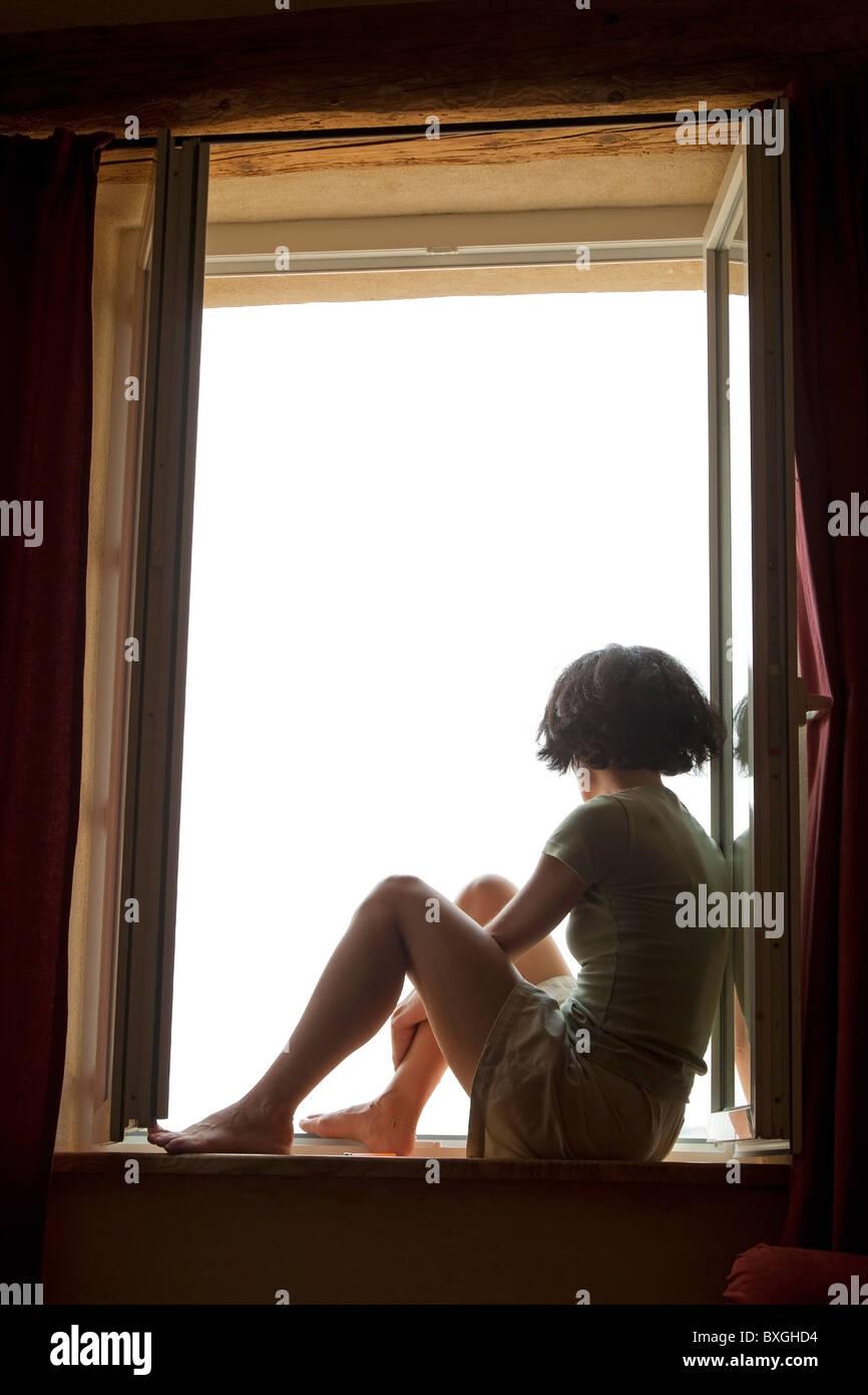 Femme assise sur le rebord de la vitre et de penser à la recherche par la fenêtre Banque D'Images