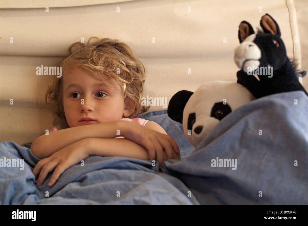 Petite fille au lit regarder la télévision entourée de ses jouets préférés. Photo Stock