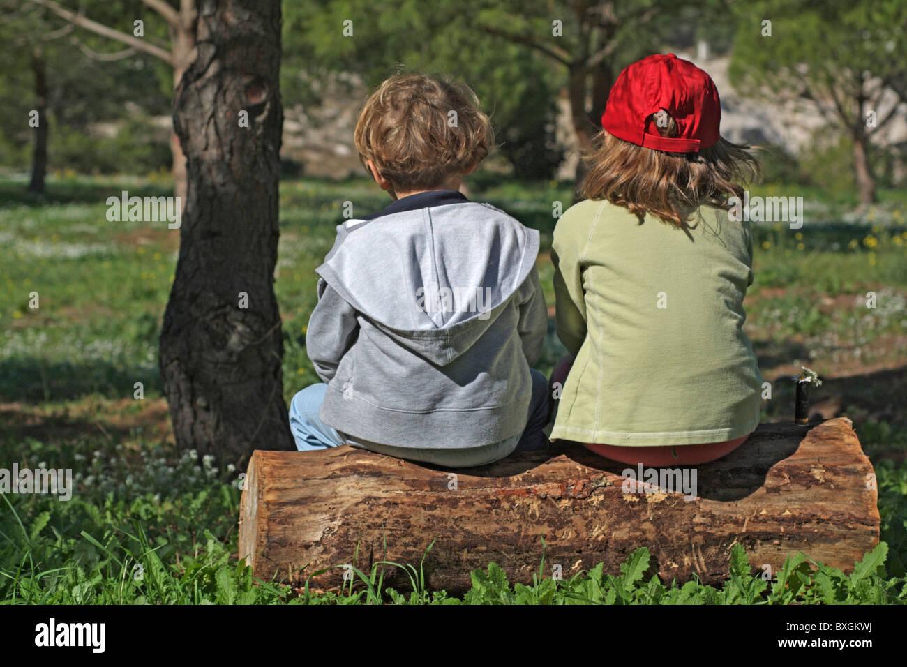 Deux petits amis assis sur un tronc d'arbre dans la forêt. Photo Stock