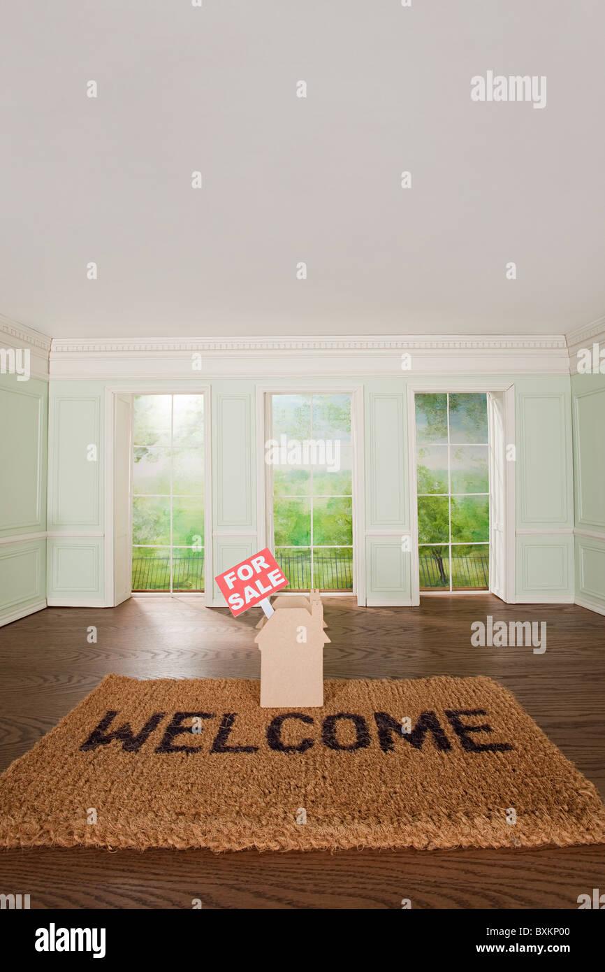 Maison à vendre et de tapis de bienvenue dans la chambre minuscule Photo Stock