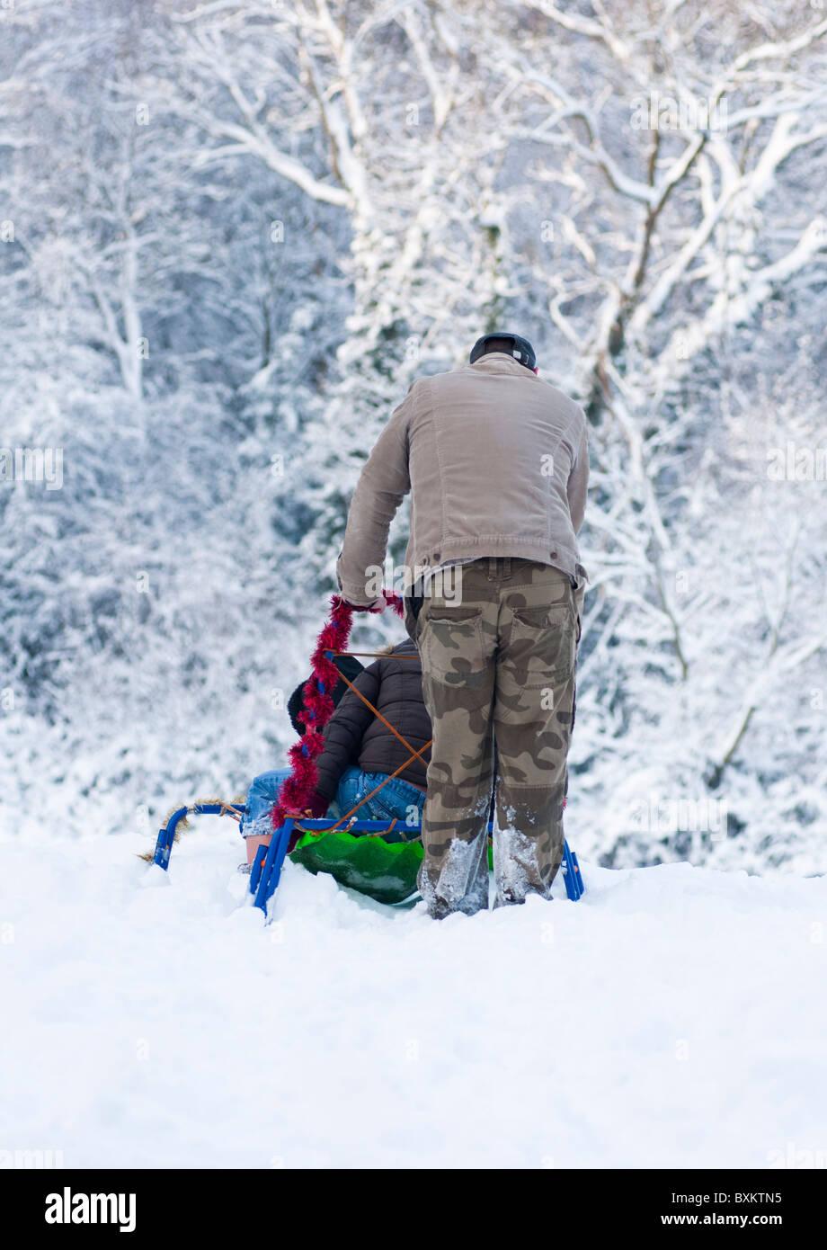 Papa pousse son traîneau d'enfant en bas de la colline dans le Worcestershire, en Angleterre, au cours de l'hiver de 2010. Banque D'Images