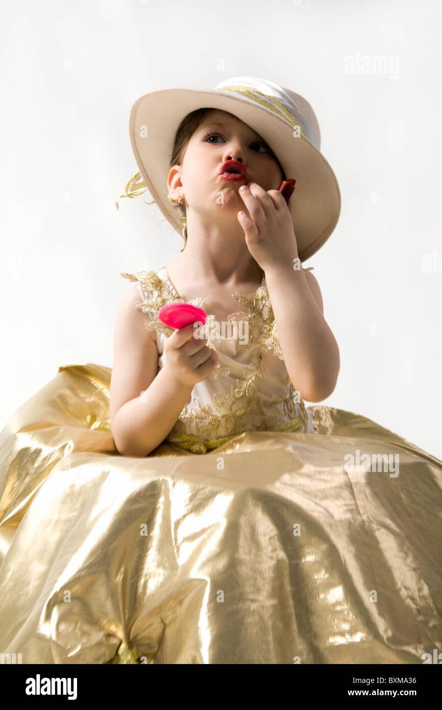 Isolated on white sweet brunette petite fille en robe de lumière dorée et white hat qui composent ses lèvres Banque D'Images