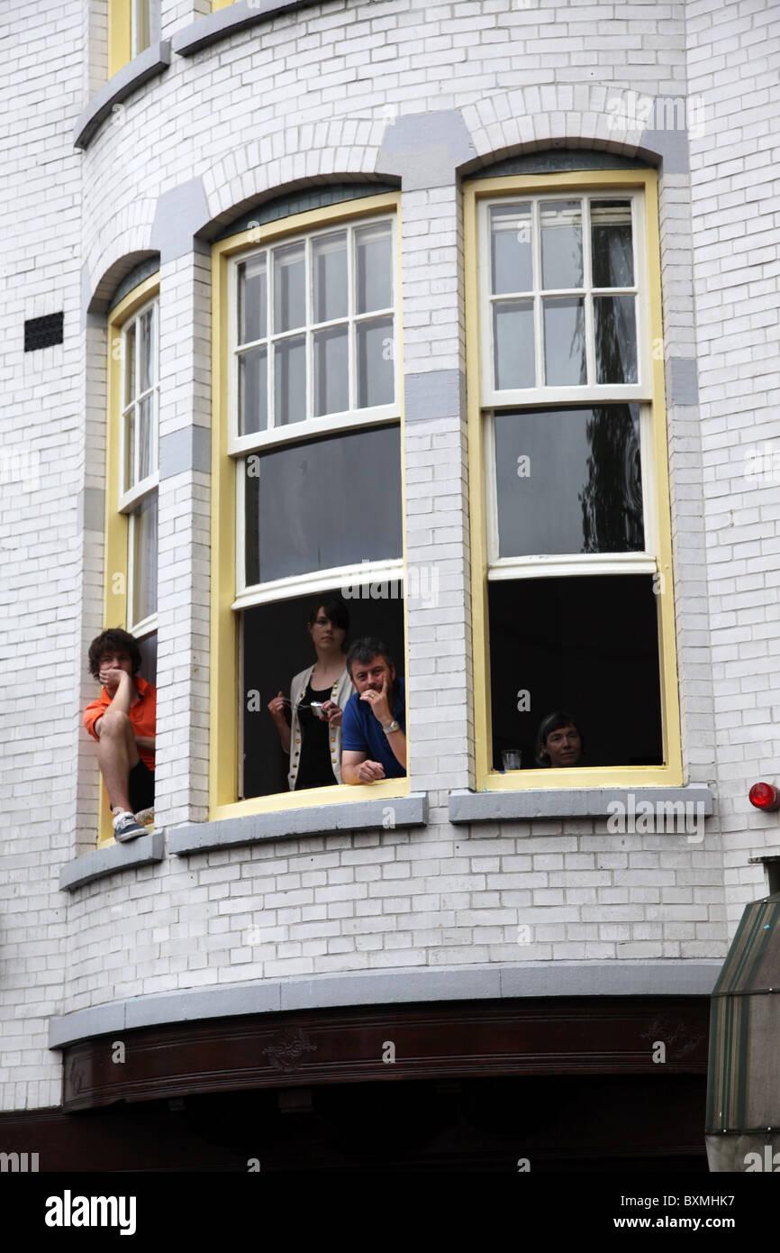 Les gens assis dans les rebords de fenêtre regardant Gay Pride 2010 Photo Stock