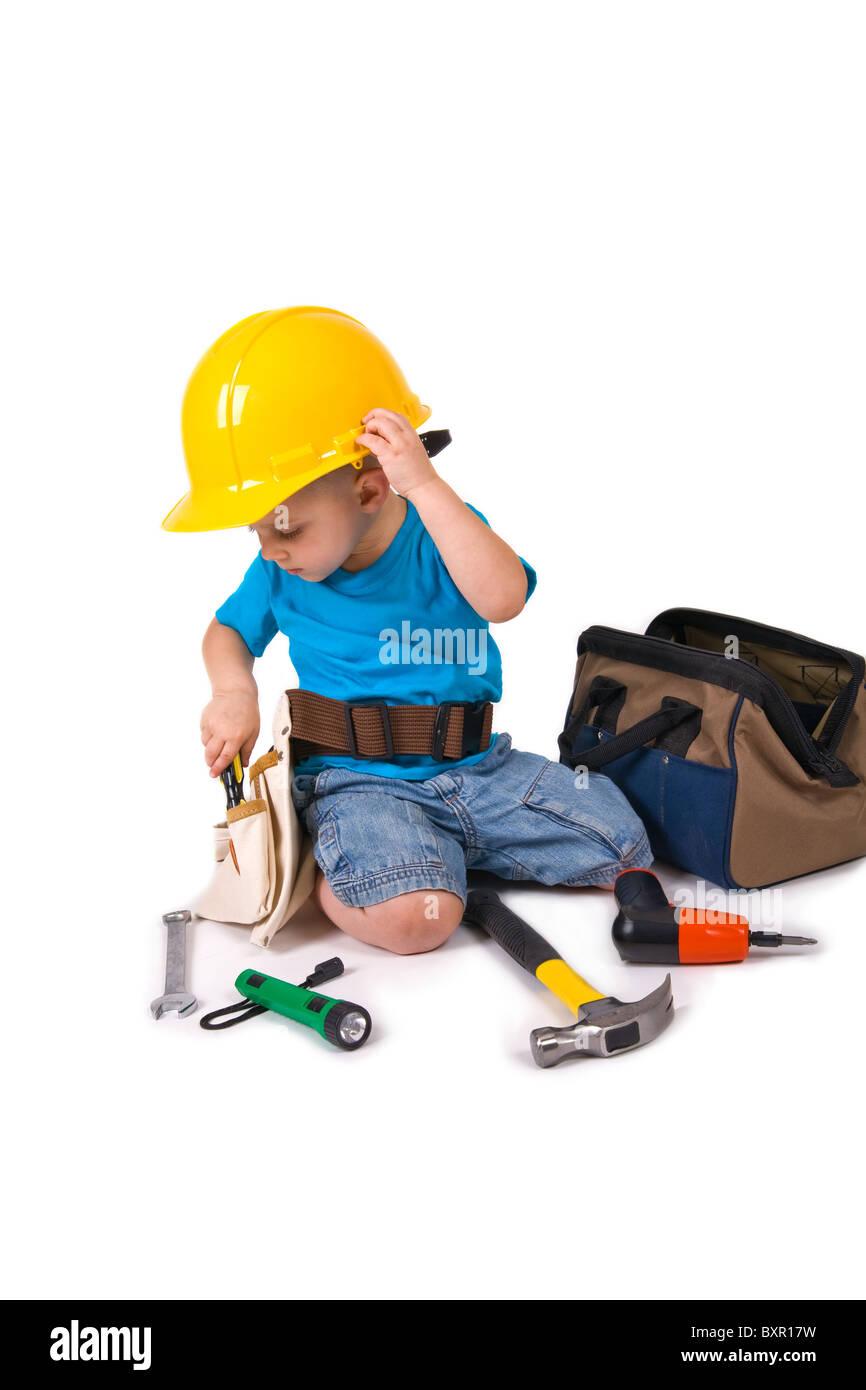 e4ebb58a0c21 Un jeune garçon portent un casque et ceinture d outils, jouant avec grandi d