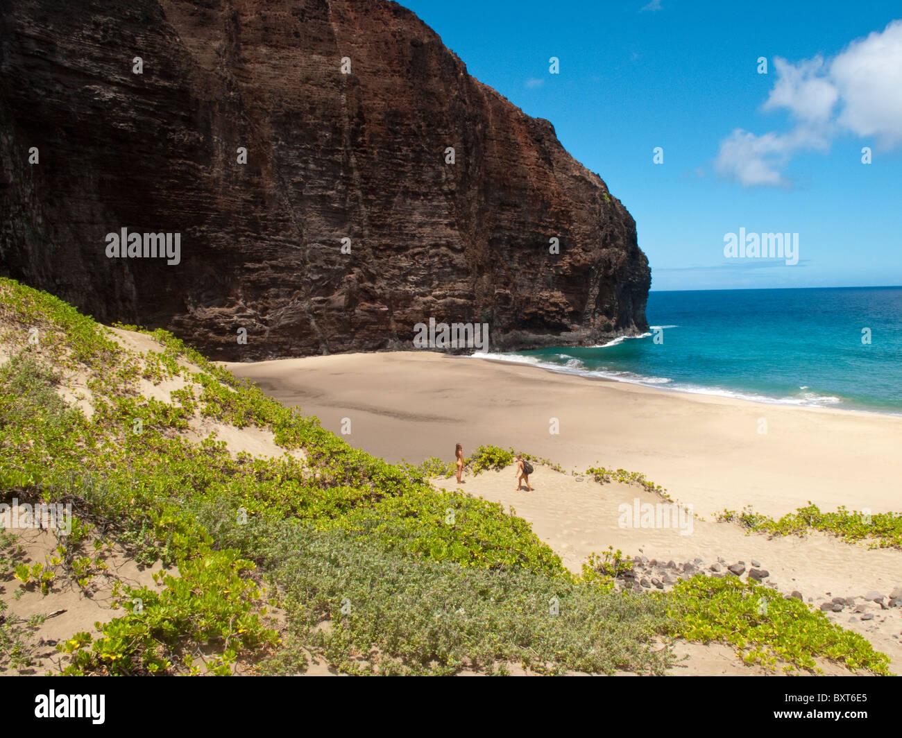Les femmes de la randonnée dans le sable à Honopu beach, côte de Na Pali, Kauai Banque D'Images
