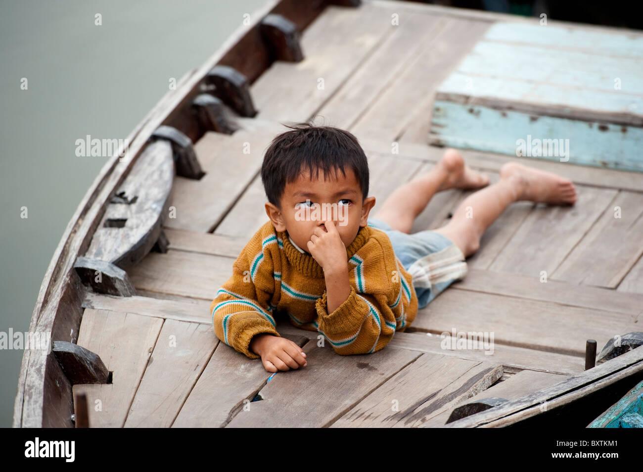 Enfant couché sur un bateau sur la rivière Thu Bon, Hoi An, Vietnam Photo Stock