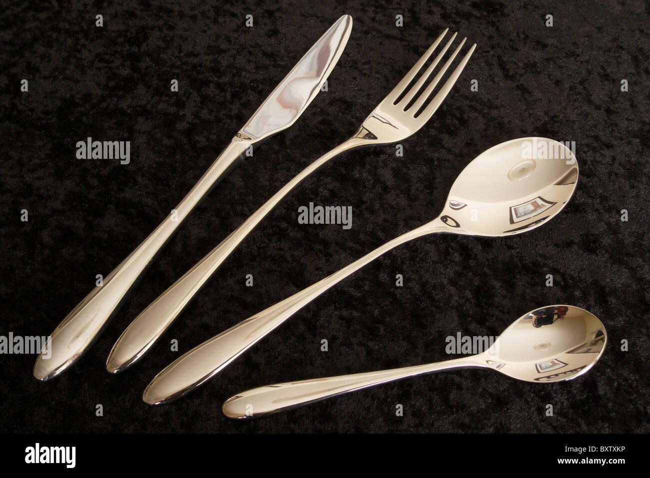 Une sélection de couverts en argent comprenant un couteau, fourchette, cuillère et cuillère à café sur un fond de Banque D'Images