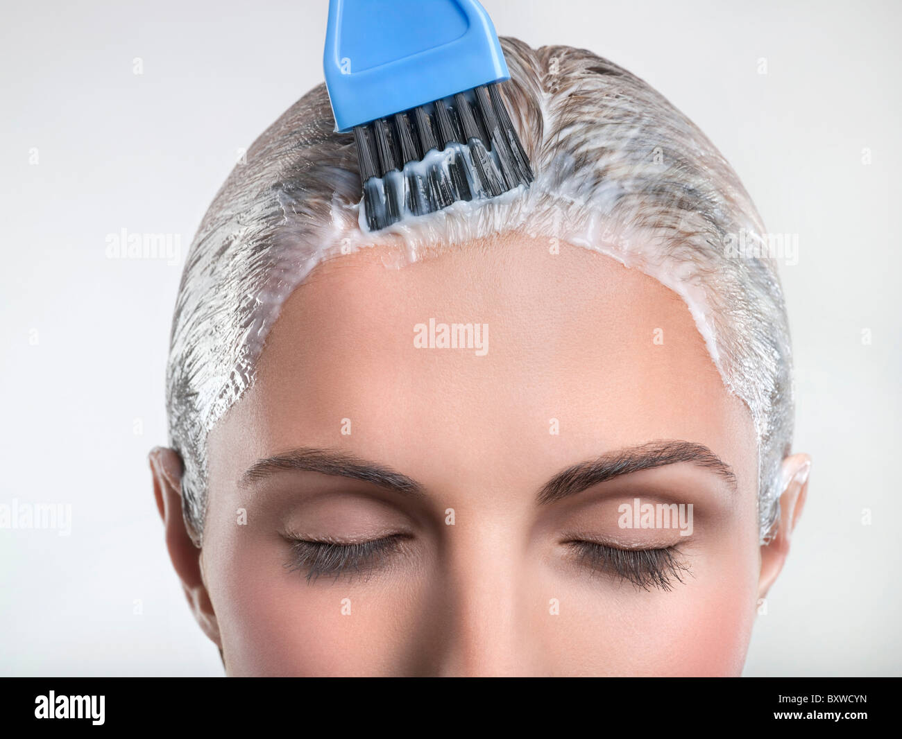 Young woman applying couleur de cheveux Photo Stock