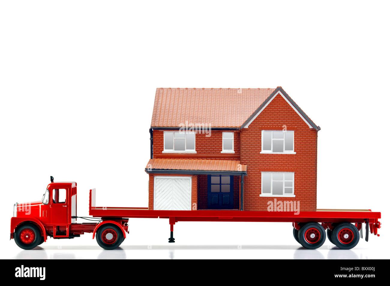 Un plateau chargé de camions avec une maison isolée sur un fond blanc. Les deux sont des modèles. Photo Stock