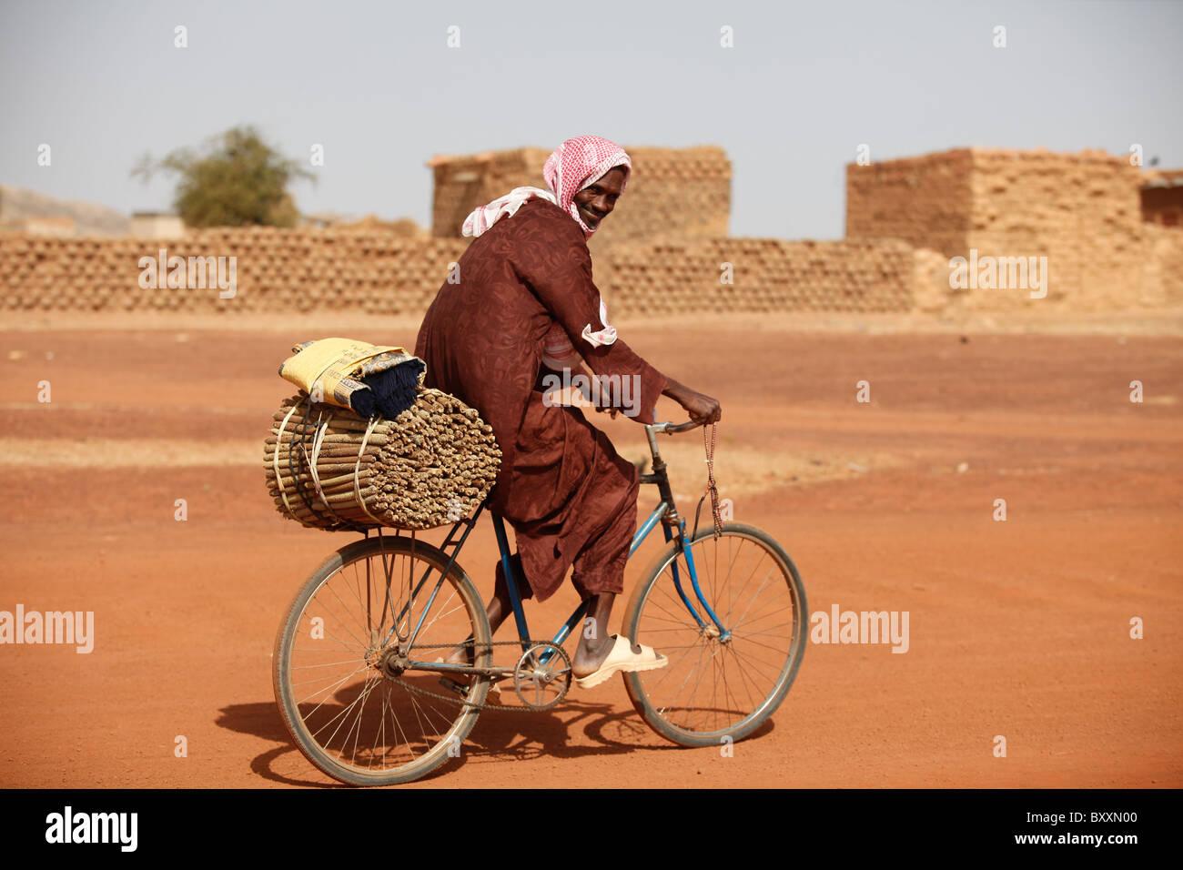 Un homme à travers la ville de Djibo, au Burkina Faso avec le mil récolté sur sa bicyclette. Photo Stock