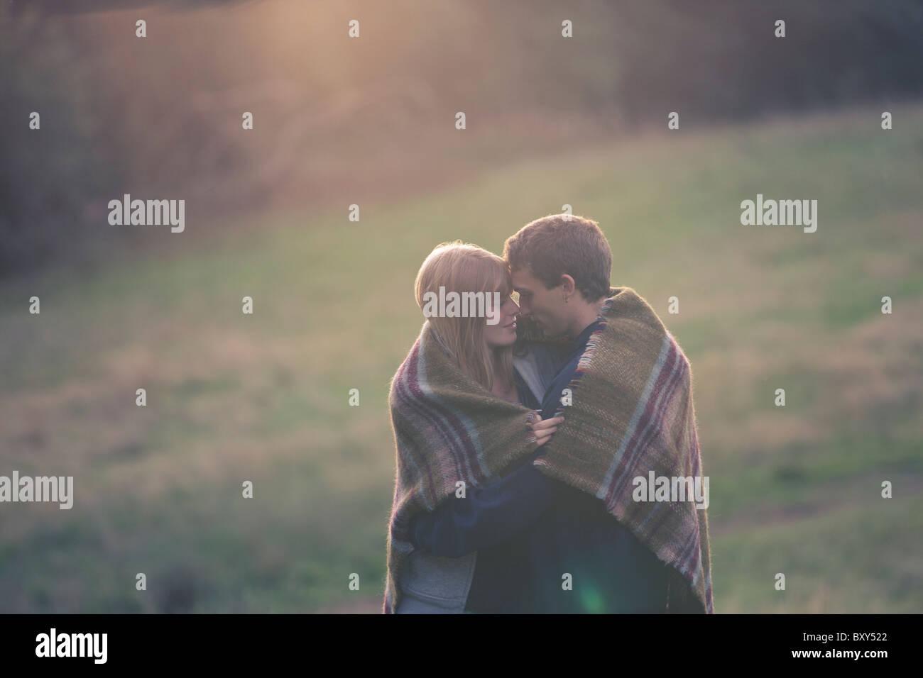 Un jeune couple embracing outdoors, enveloppé dans une couverture Photo Stock