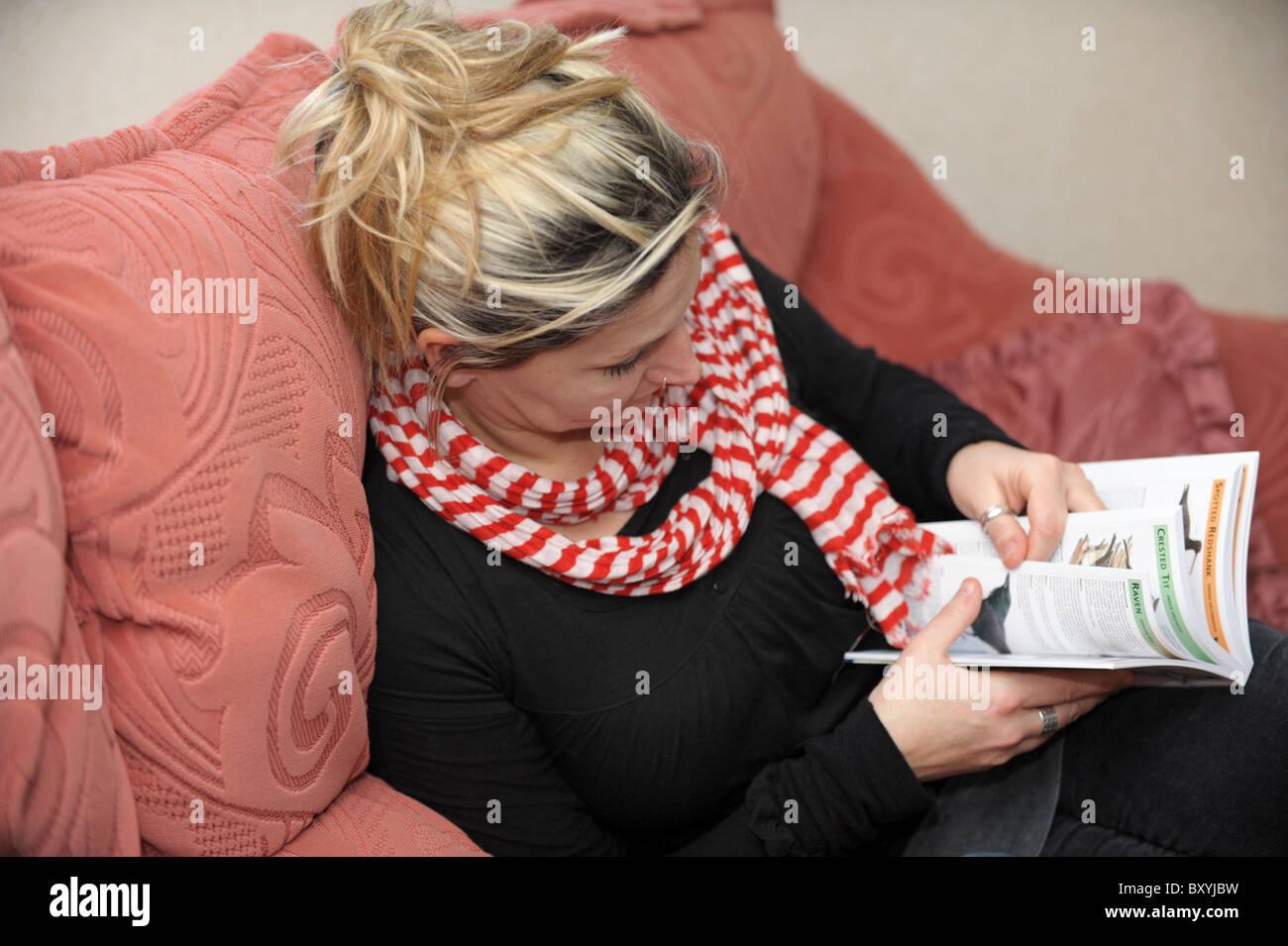 Blonde-haired woman wearing scarf dénudée et haut noir est assis sur un  canapé à 234b8ee56f4