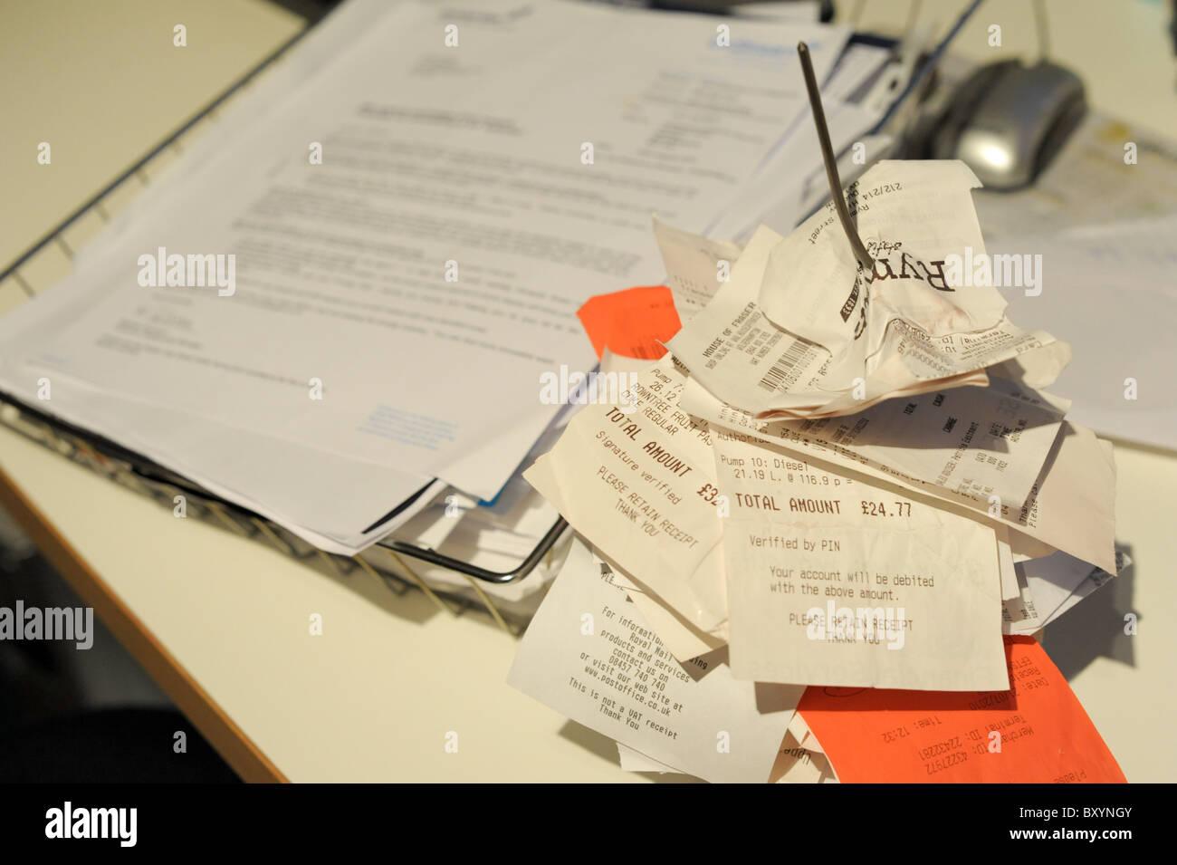 Les reçus et factures à un pic dans un bureau sur un bureau prêt à être traité avec Photo Stock
