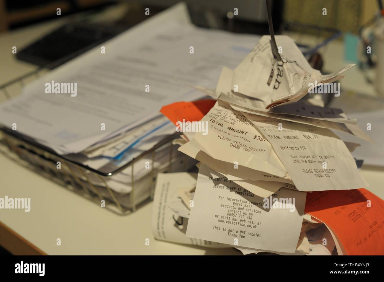 Les reçus et factures à un pic dans un bureau sur un bureau prêt à être traitées pour Photo Stock