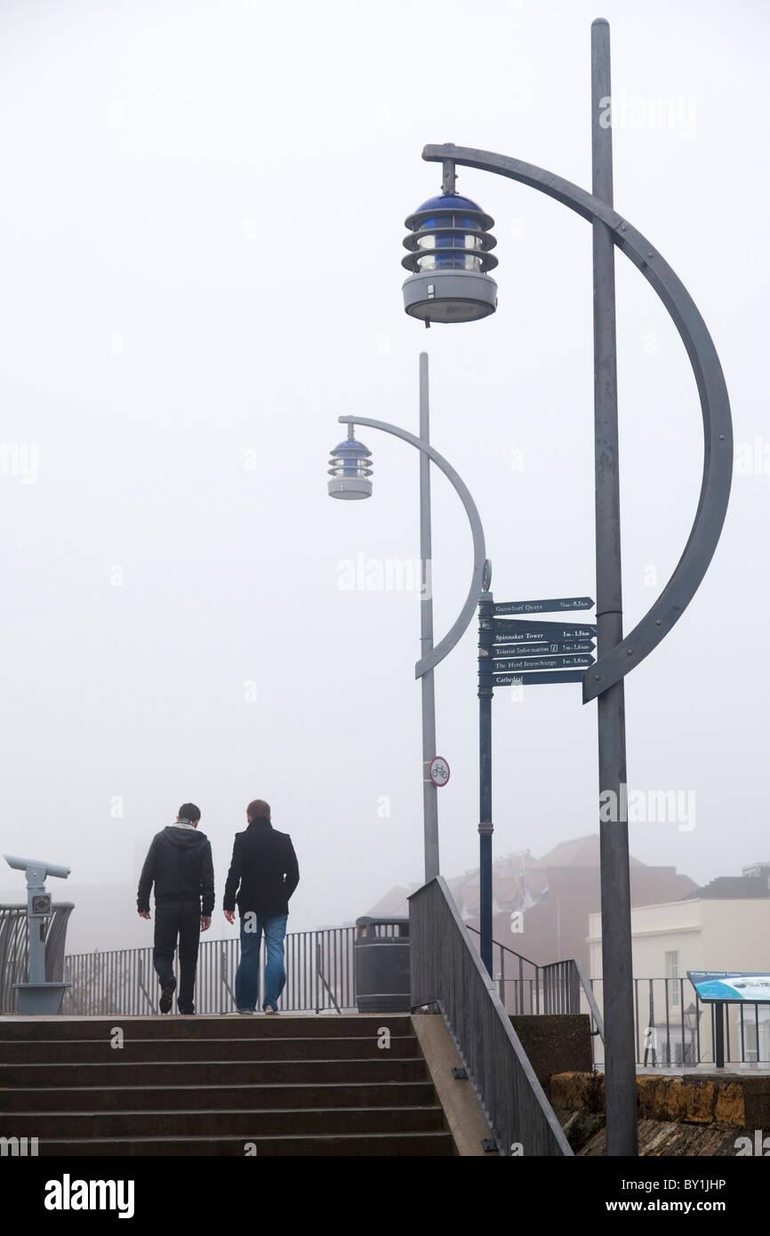 Marcher sur le mur de la mer dans le brouillard avec les lampes de rue Photo Stock