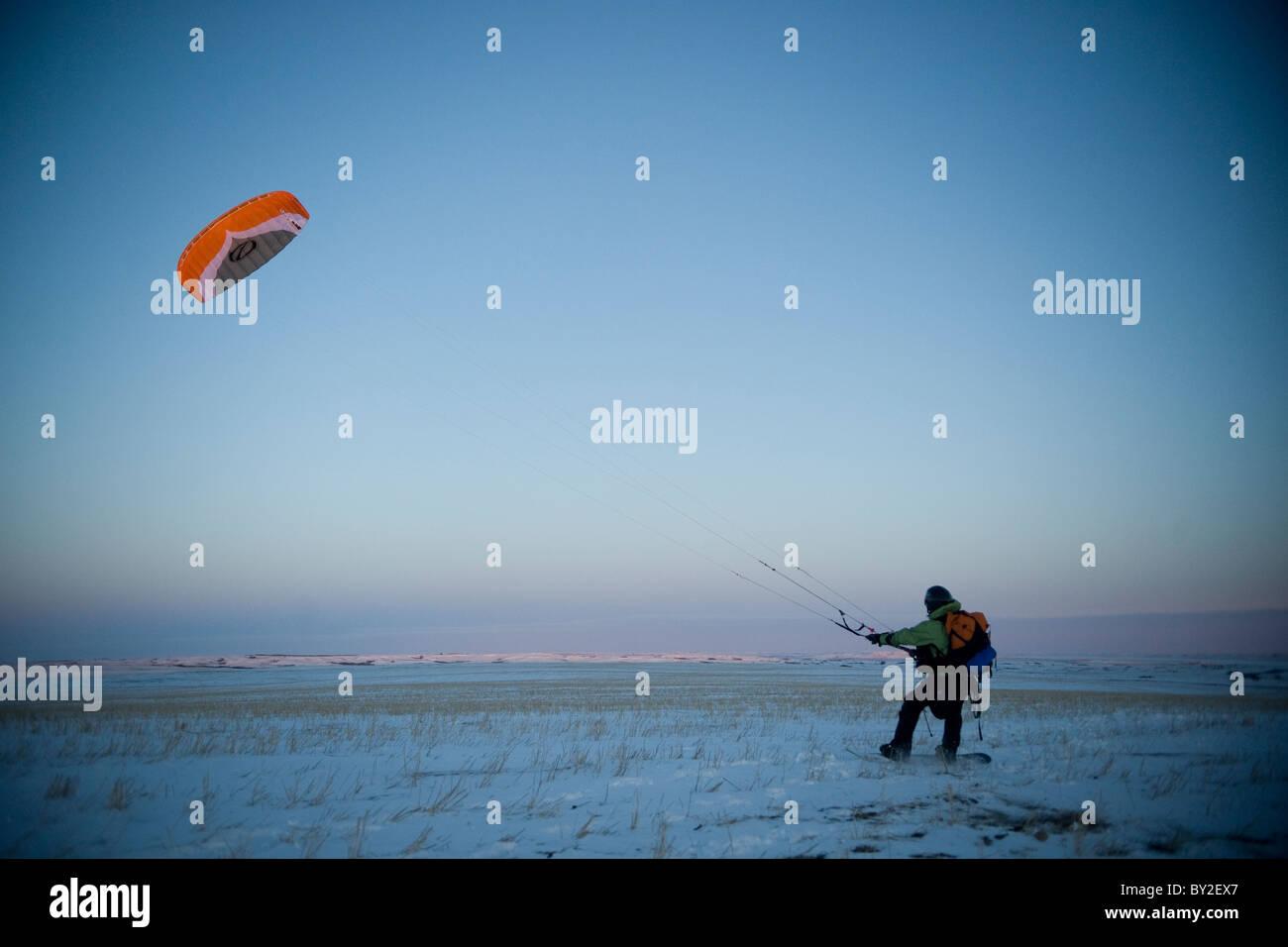 Un jeune homme qui décolle avec son snowkite. Photo Stock