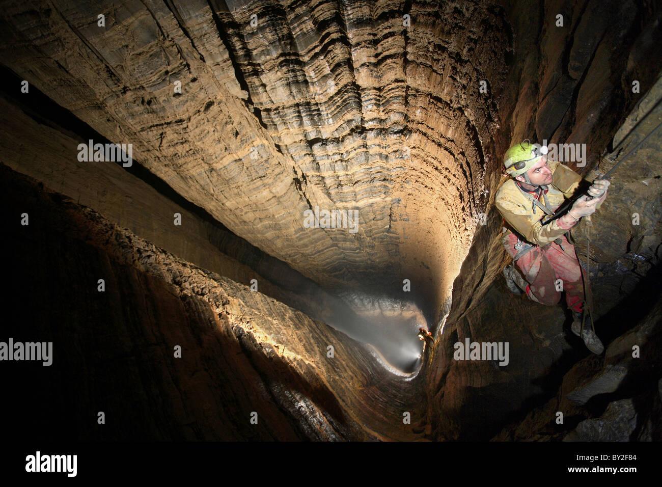 Un homme monte sur les cordes dans le plus grand arbre du monde souterrain appelé Miao Keng en Chine. Banque D'Images