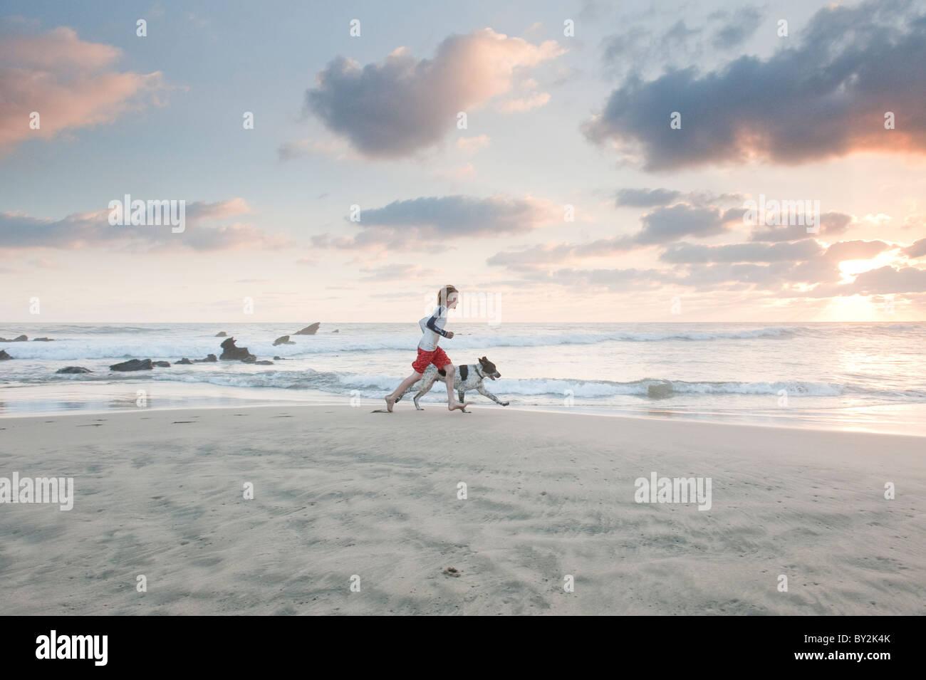 Un jeune garçon et le chien courir le long d'une plage tranquille, dans le Mexique au coucher du soleil. Photo Stock