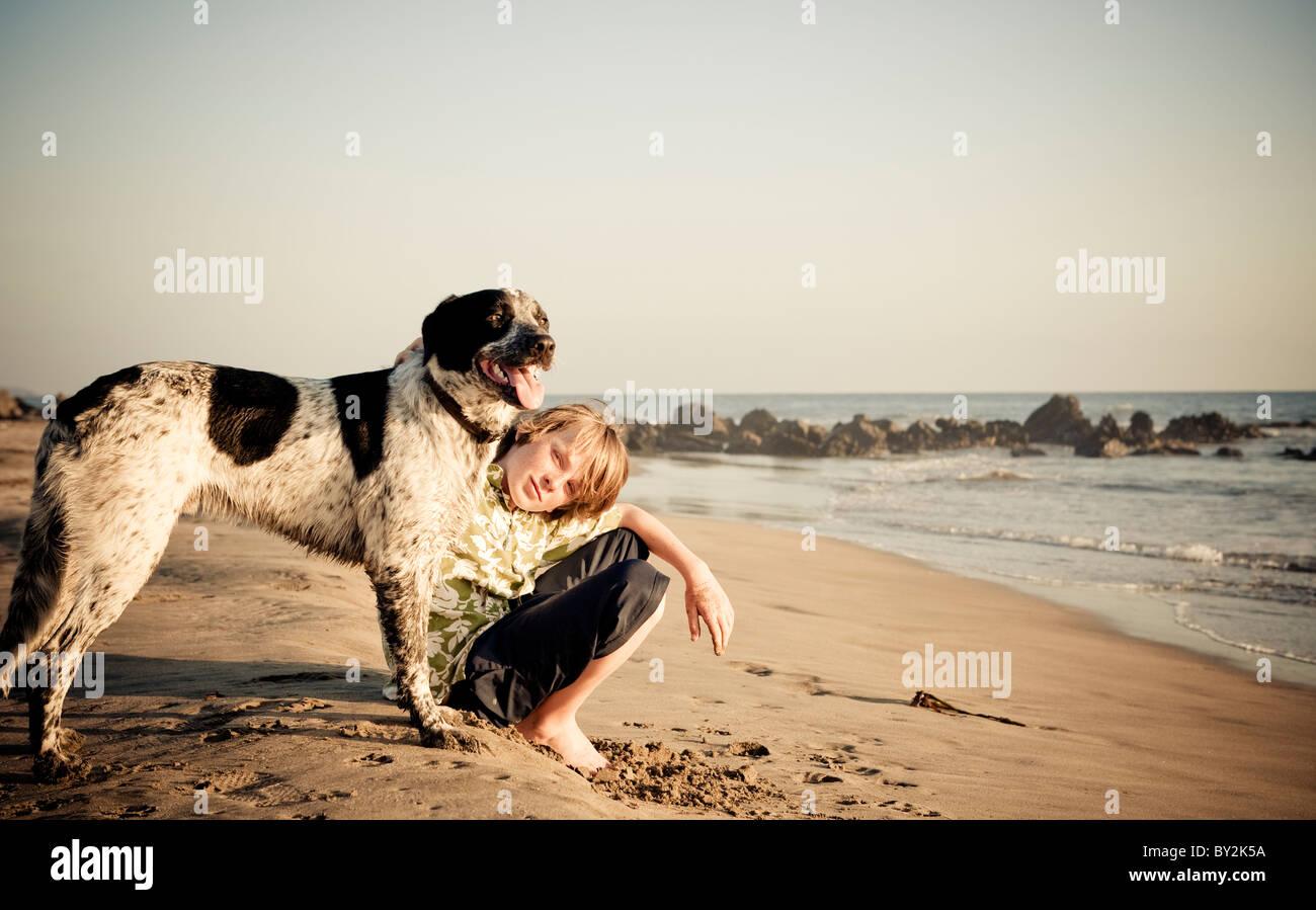 Portrait d'un jeune garçon et son chien au coucher du soleil sur une plage tranquille au Mexique. Photo Stock