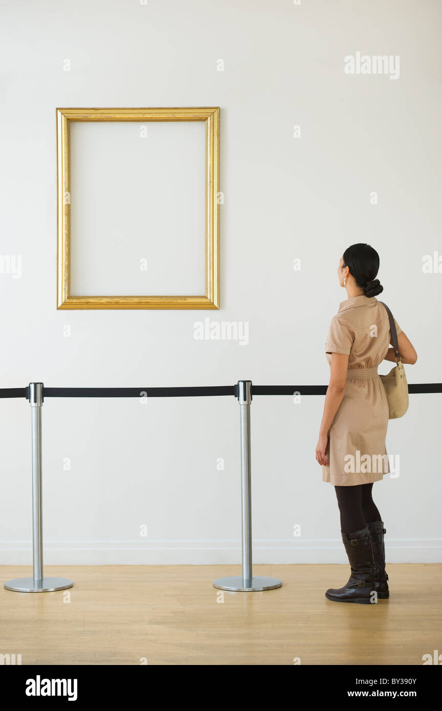 Woman looking at blank en cadre photo art gallery Photo Stock
