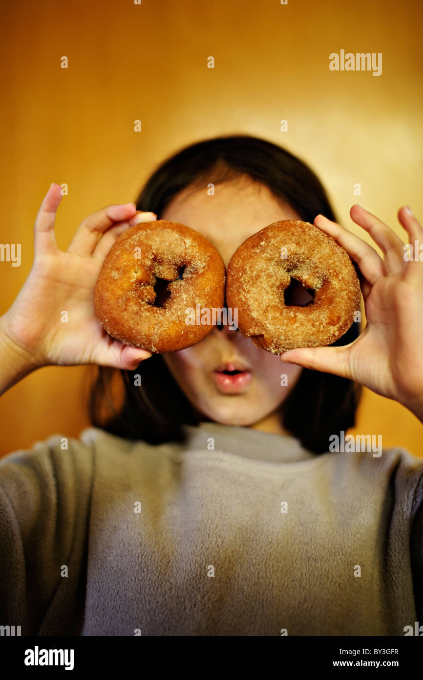 Girl holding donuts au-dessus des yeux. Photo Stock