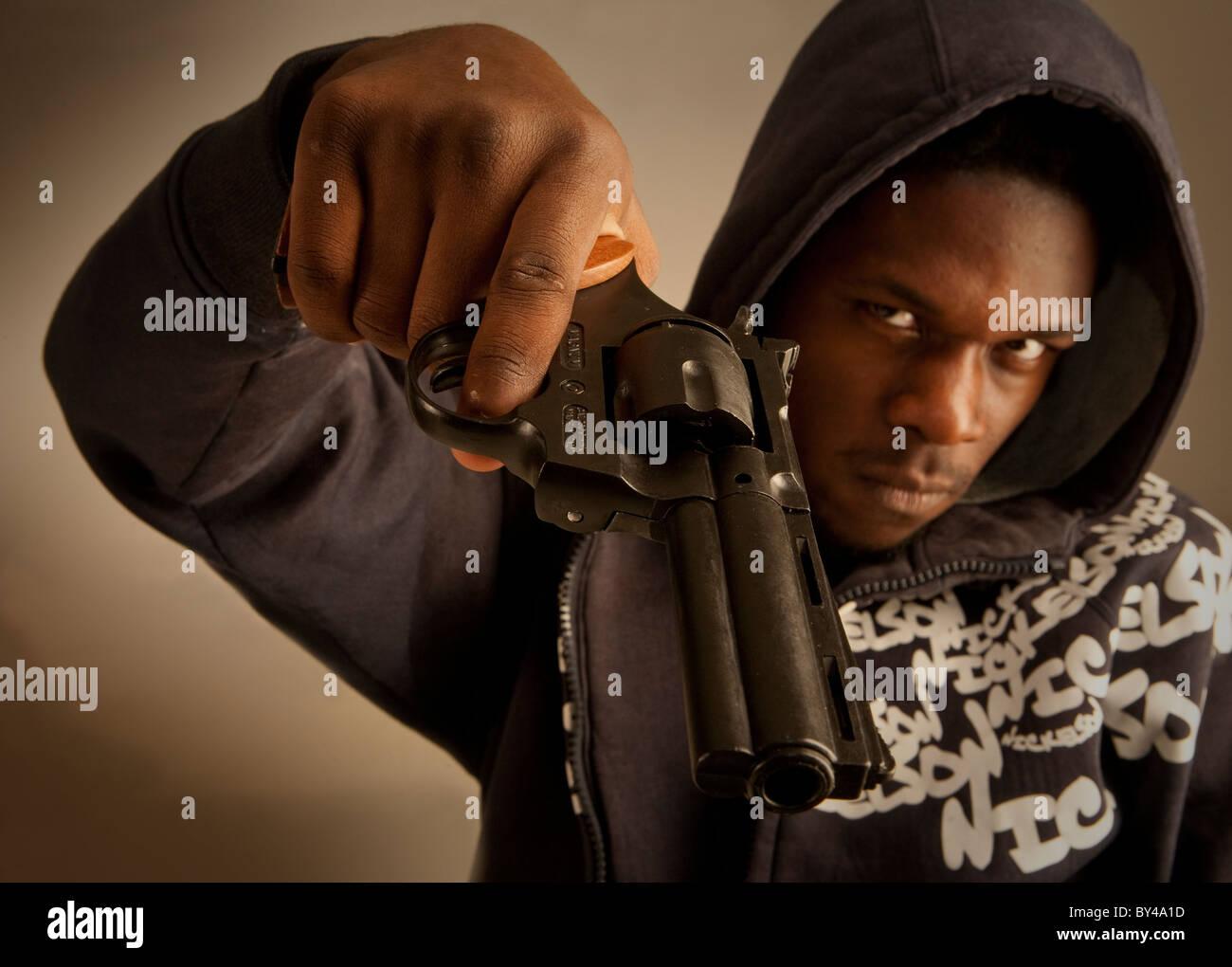 Jeune homme noir model posing with a gun Banque D'Images