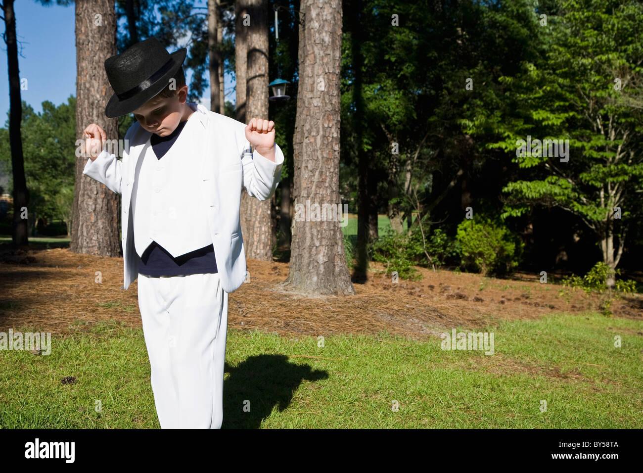 e99e62ffc17d5d Un jeune garçon dans un costume blanc danser comme Michael Jackson, à  l extérieur