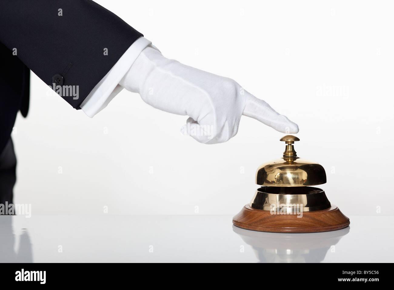 Un majordome en appuyant sur un service bell, focus on hand Photo Stock