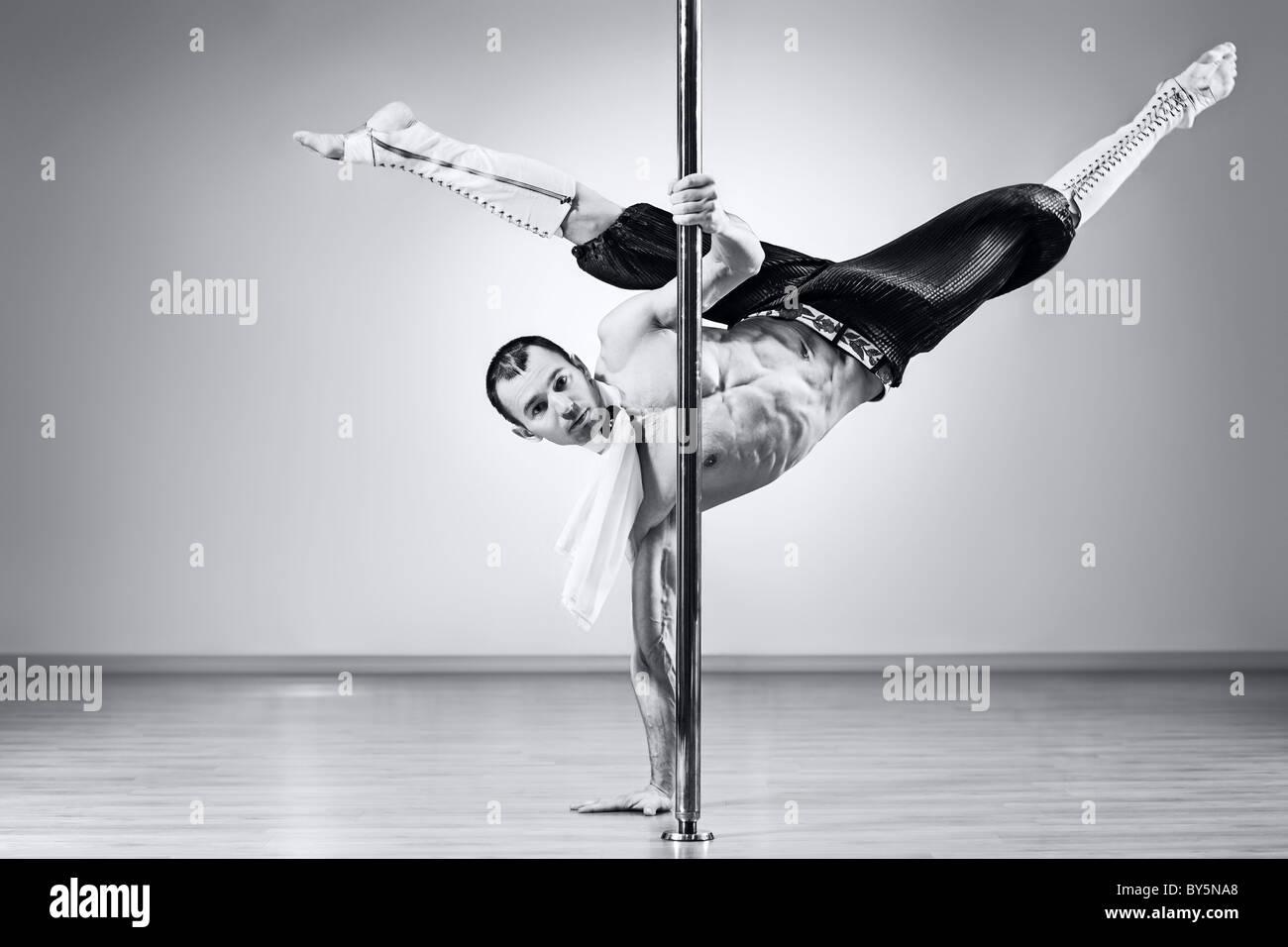 Les jeunes pole dance homme fort. Les couleurs noir et blanc. Photo Stock