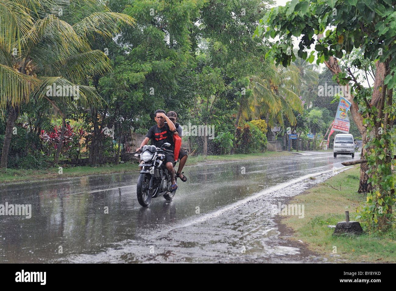 Les hommes asiatiques équitation une moto à travers une douche de pluie Photo Stock