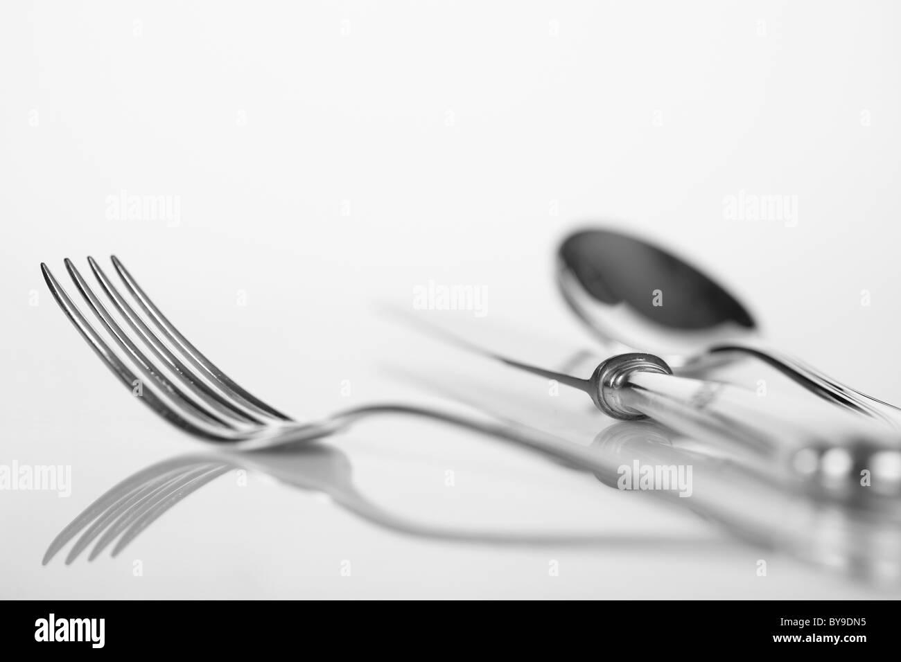 Cuillère, fourchette et couteau sur une surface réfléchissante, couverts Photo Stock
