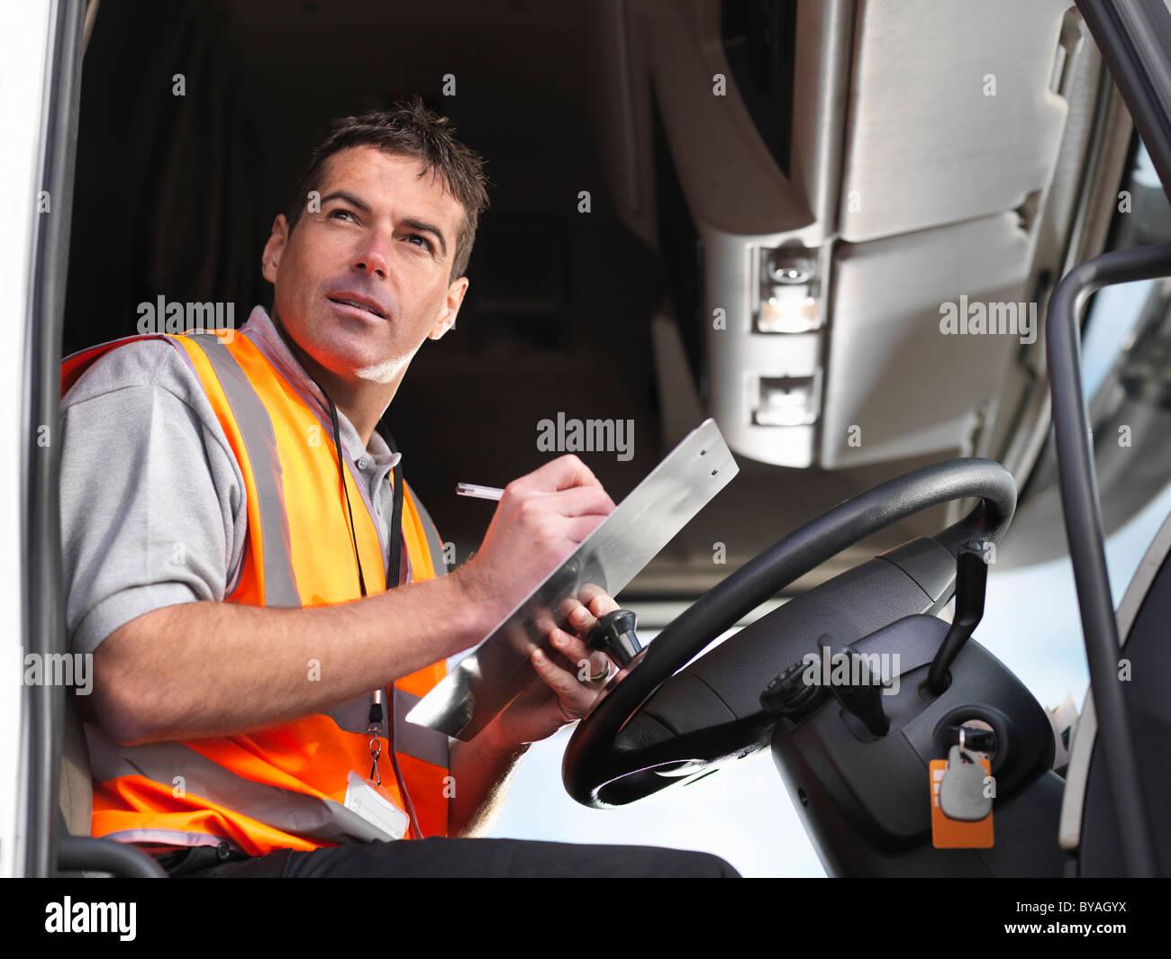 Chauffeur de camion prend des notes dans la cabine du camion Photo Stock