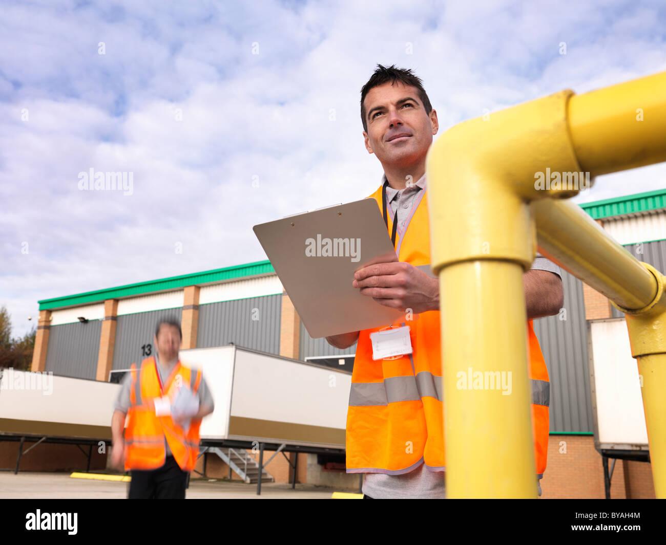 Les travailleurs de la zone de chargement avec les presse-papiers Photo Stock