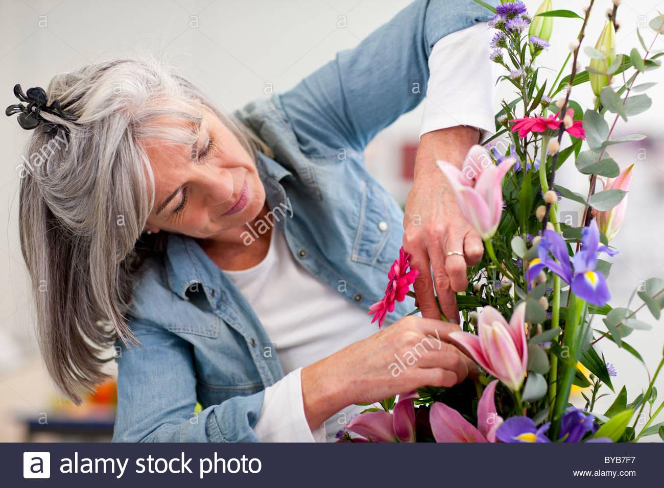 Femme sérieuse mettant en fleurs bouquet de fleurs en classe Photo Stock