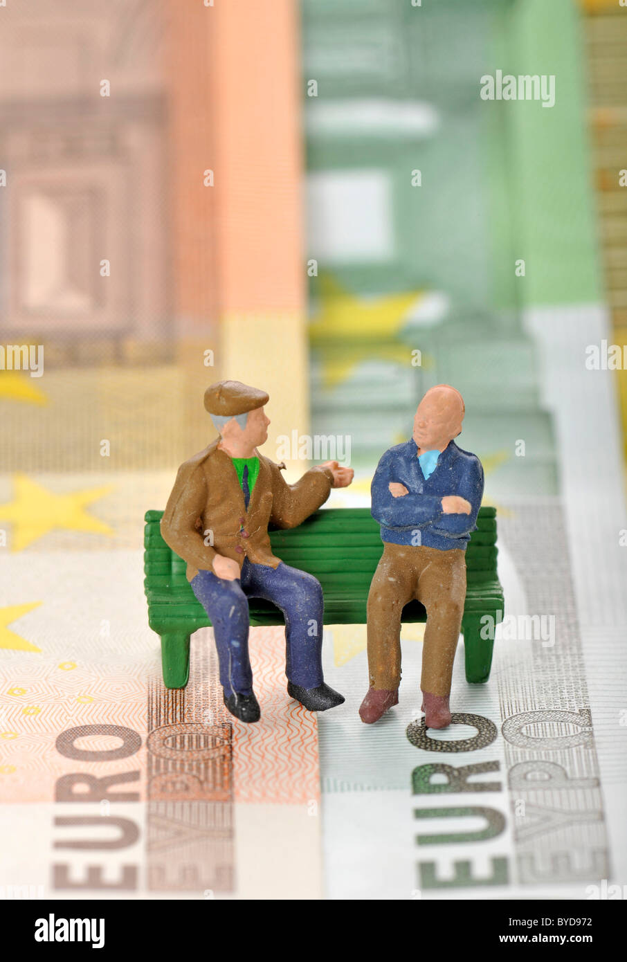 Figures miniatures de personnes âgées sur un banc de parc sur divers billets, image symbolique pour pension Photo Stock