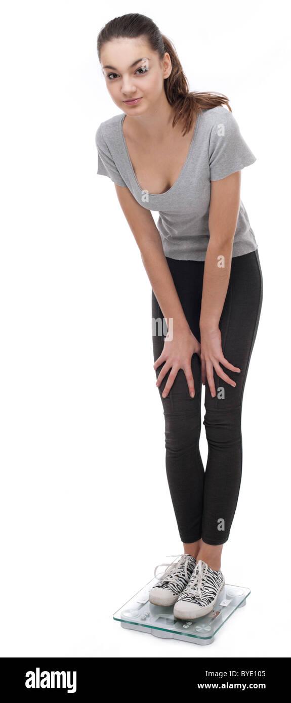 Adolescent debout sur un pèse-personne. Isolé sur un fond blanc. Photo Stock