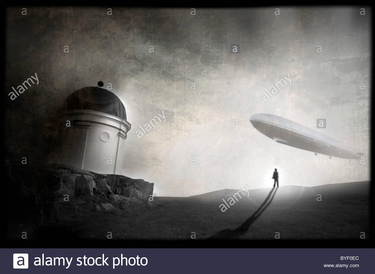 Un homme debout près d'une falaise est à la recherche d'un vol zeppelin vers lui Photo Stock