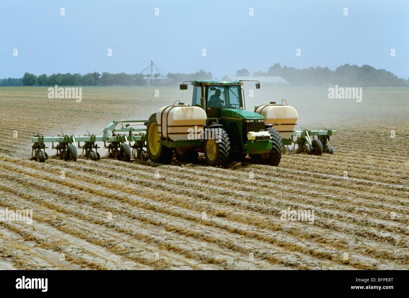 Un tracteur et 12 rangs, mettre en œuvre des bandes et middles cultive le Roundup Ultra Max herbicide sur les lignes Photo Stock