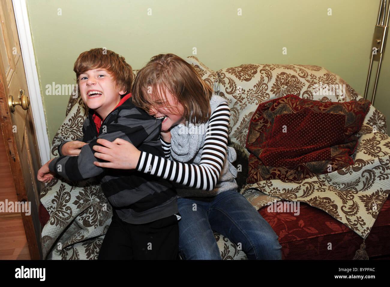 Une soeur et son frère se battre dans le salon MODEL PUBLIÉ Photo Stock
