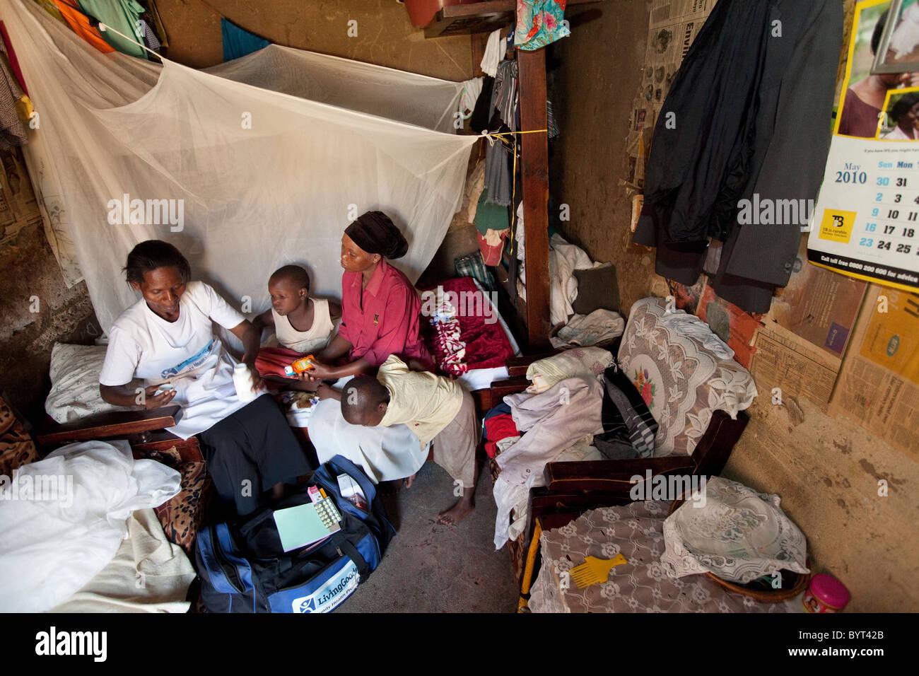 Un travailleur des services de soins de santé communautaire visites une famille séropositif dans un bidonville Photo Stock