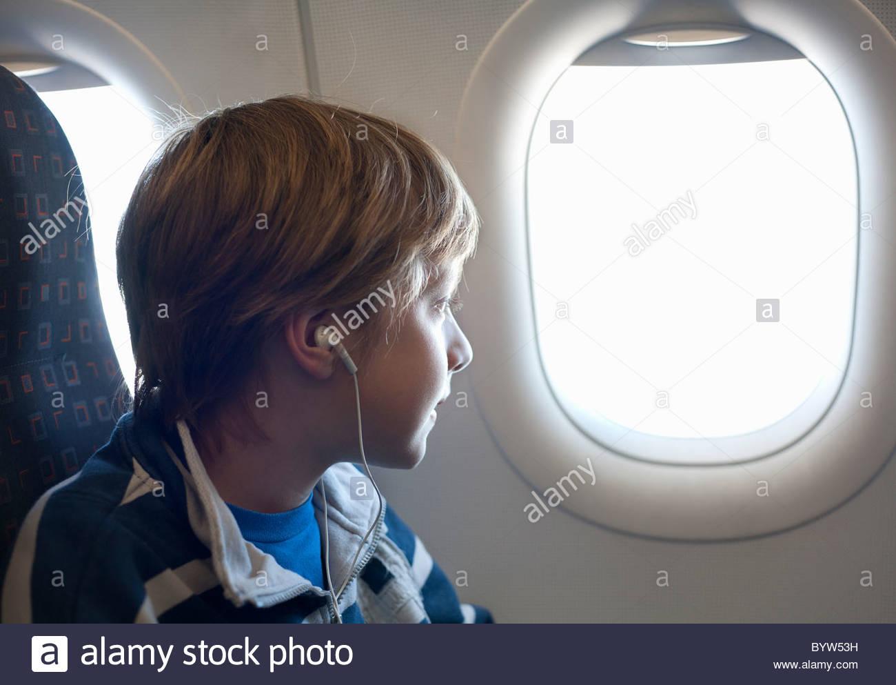 Le garçon à la fenêtre de l'avion Photo Stock