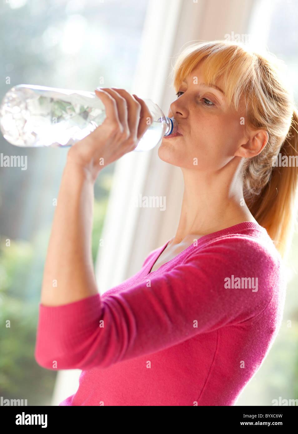 Femme buvant de l'eau en bouteille Photo Stock