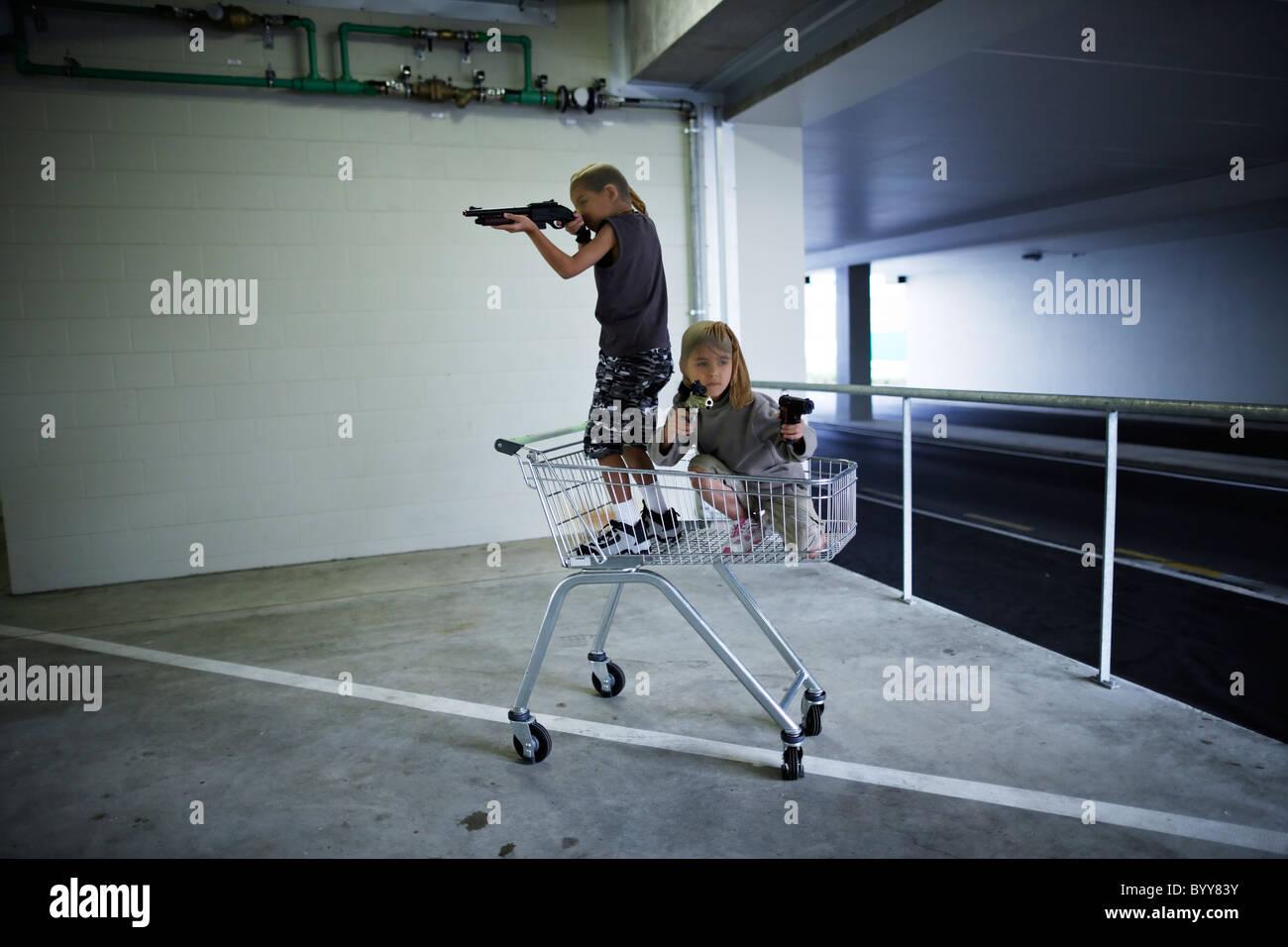 Les enfants avec les masques et les armes-jouets dans parking souterrain se préparer à grand hold-up. Photo Stock