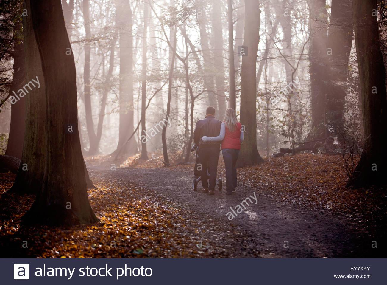 Un jeune couple en poussant une poussette dans le parc, vue arrière Photo Stock