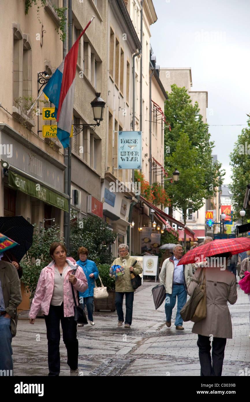 Les piétons marcher sous la pluie sur une rue piétonne dans la ville de Luxembourg, Luxembourg. Photo Stock