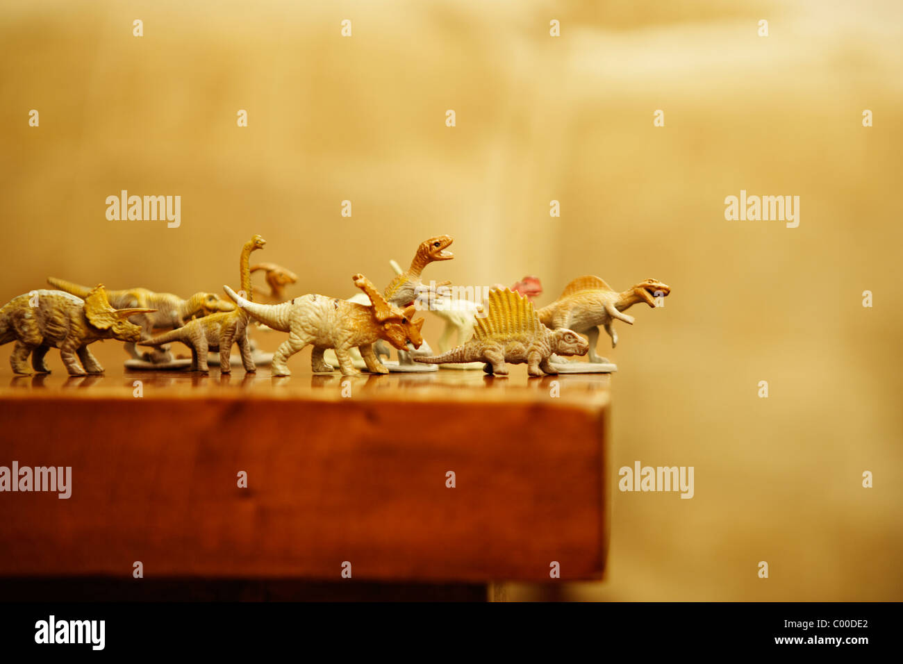 Dinosaures jouets se précipiter le rebord d'une table Banque D'Images