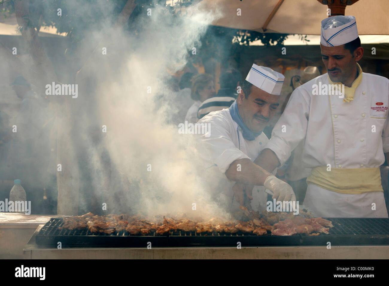 Cook au restaurant du bassin prepearing poulet grillé, Petra, Jordanie. Photo Stock