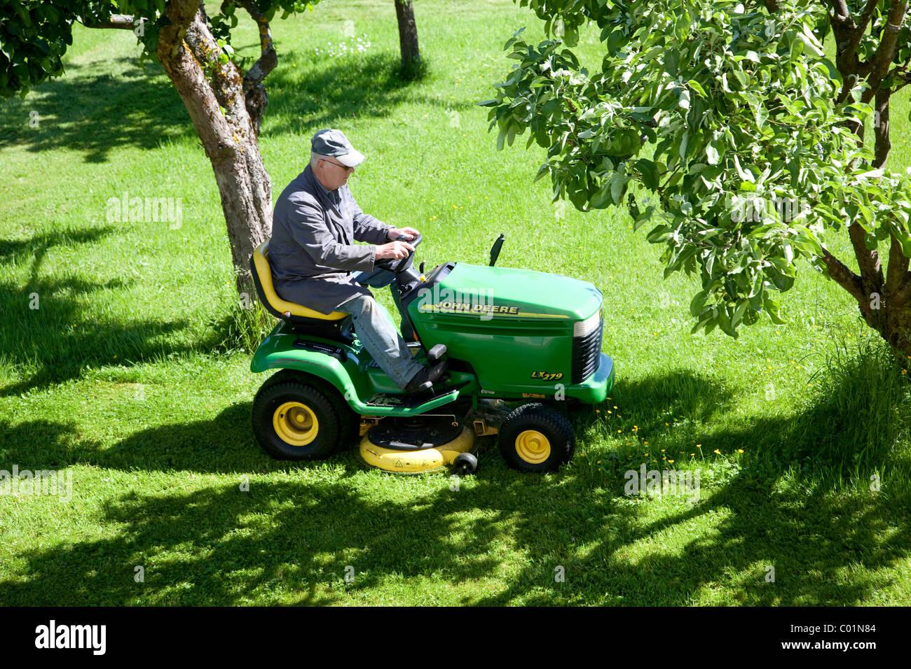 homme âgé de tondre la pelouse sur un john deere tondeuse à siège