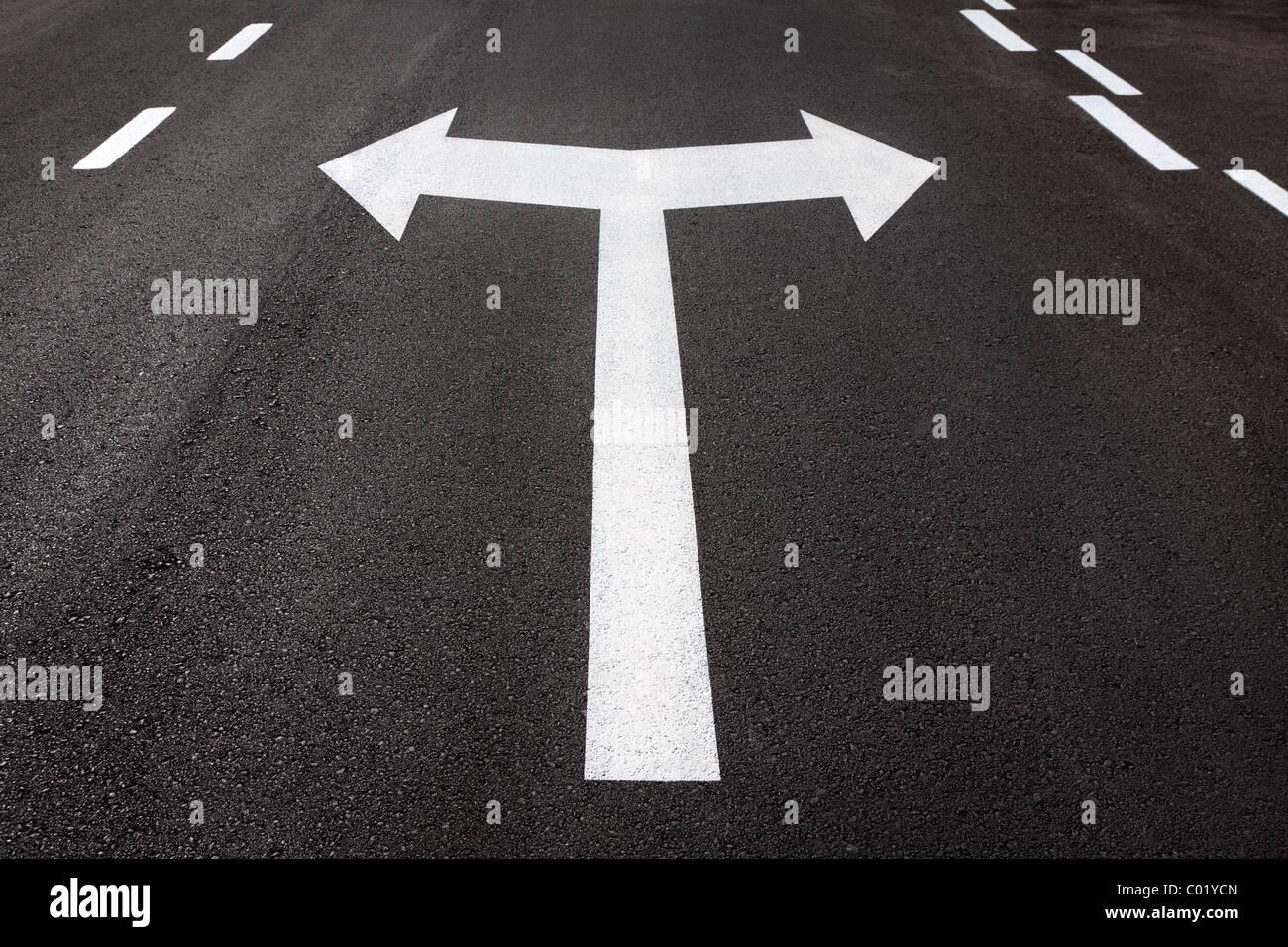 Flèches gauche et droite peint sur la chaussée goudronnée. Concept pour tourner, décision, choix, Photo Stock